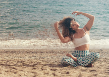 Young Woman Sitting On The Beach And Arranging Her Hair - Dispersion Effect