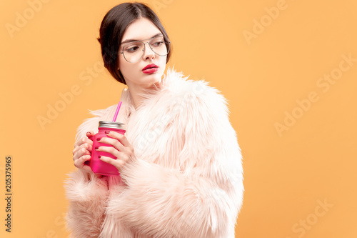 Fotografia, Obraz Glamour young woman with pink drinking jar looking away on yellow background