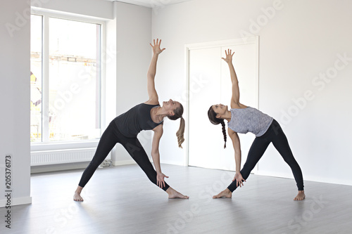 Two women doing triangle yoga pose together Poster