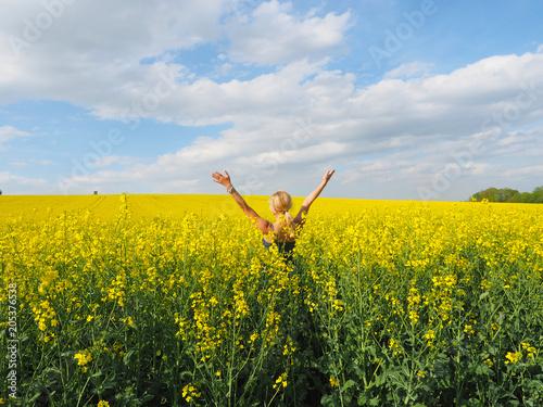 Frau im Rapsfeld genießt den Frühling