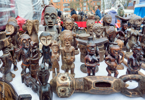 Many african totem figures of spirits for sale on flea market with antique stuff and vintage decor
