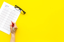 Take The Exam, Write The Exam. Hand With Pen Near Exam Paper On Yellow Background Top View Copy Space