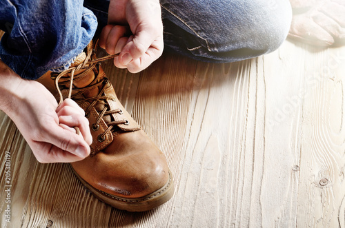 Fotografía  Carpenter in blue jeans tying shoelaces of yellow work boots on on wooden floor