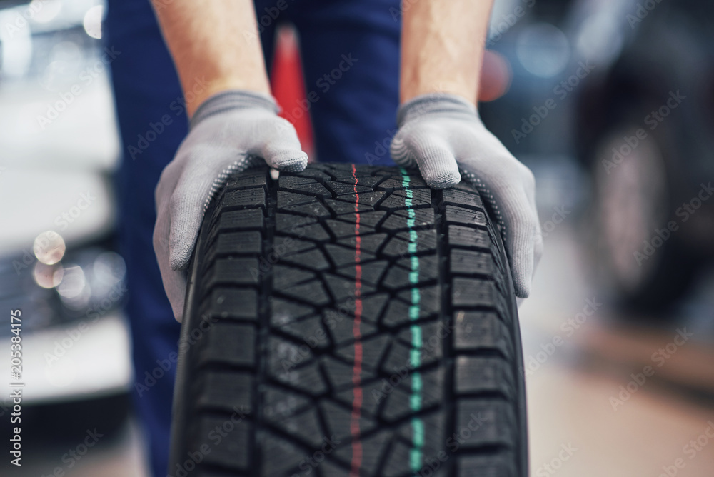 Fototapety, obrazy: Closeup of mechanic hands pushing a black tire in the workshop