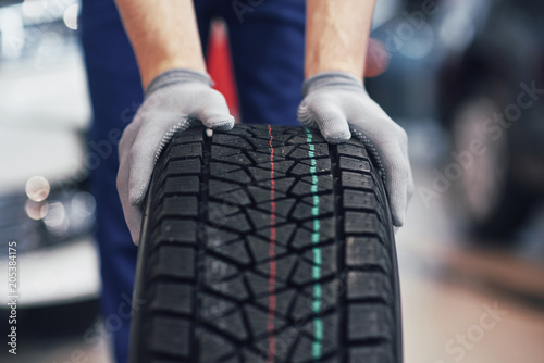 plakat Closeup of mechanic hands pushing a black tire in the workshop
