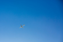 Passenger Airplane Flies Overhead On Clear Blue Sky Background With No Clouds. Bottom View