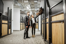 Young Couple Riders In Leather Jackets Standing With Horse In The Beautiful Stable