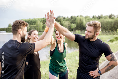 Foto  Sports team having fun putting hands together after the training outdoors in the