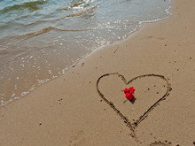 Red Flower And A Heart Sign On Yellow Sand And Clear Water. Tropical Background.