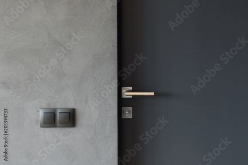 Light switch on the gray textured wall next to the door with metallic handle Fotobehang
