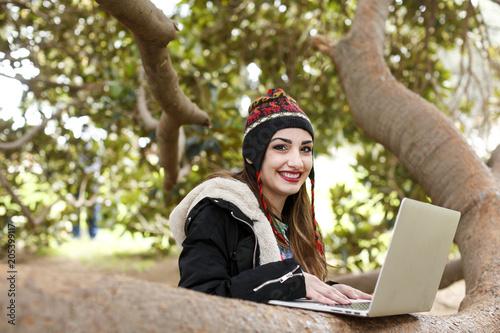 Valokuva  Giovane studentessa con cappuccio tipico lavora al computer immersa nella natura