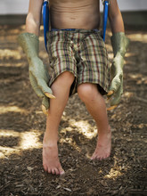 Monster Hands And Plaid Shorts Sitting On A Swing Set And Playing In A Park