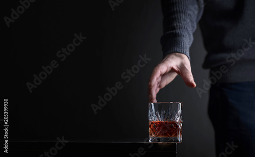 Man's hand reaches for a glass of alcohol. Canvas Print