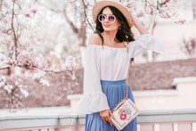 Outdoor Portrait Of Young Beautiful Woman Wearing Stylish Round Sunglasses, Straw Hat, Cold Shoulder Blouse, Pleated Skirt, With Small White Bag. Spring Fashion Concept. Copy, Empty Space For Text