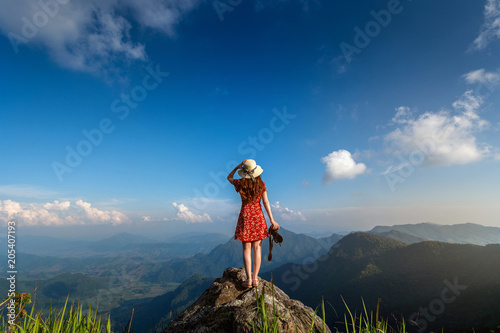 Poster Lieu connus d Asie Woman hand holding camera and standing on top of the rock in nature. Travel concept.