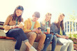technology, internet and people concept - group of happy teenage friends with smartphone and coffee cups outdoors