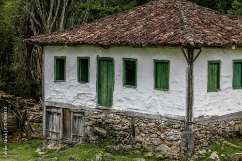 Old settler house in green landscape Fototapet