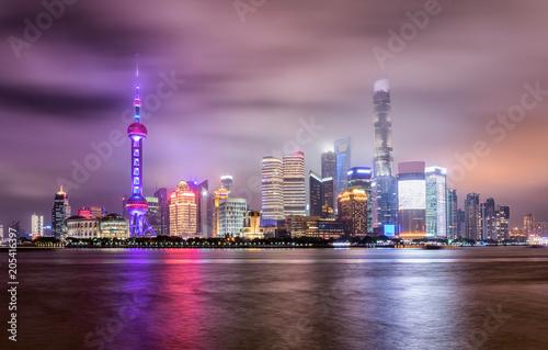 Die bunt beleuchtete Skyline von Shanghai, China, an einem bewölktem Abend