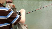 Young Boy Fishing Off Dock