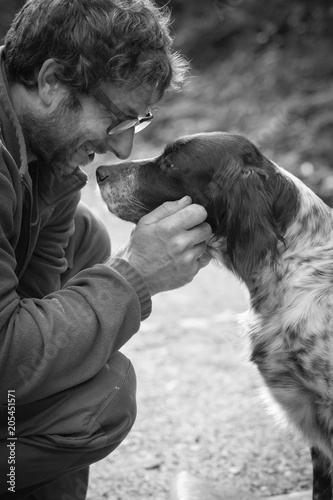 Fotografía  man's affection for his english setter dog in black and white