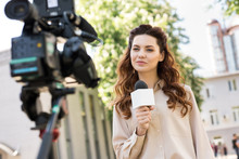 Beautiful Female Journalist With Microphone Talking To Digital Video Camera