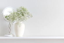Home Interior, Floral Decor. Beautiful Flowers In A Vase On A White Wall Background. White Flowers Of Gypsophila, Mirror On A Wooden Shelf.