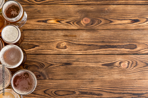 Frothy pints of beer on timber bar with copy space Fotobehang