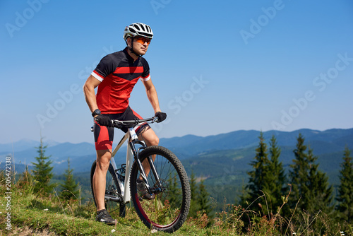 Cadres-photo bureau Cyclisme Young athletic professional sportsman starting cycling bike on top of hill. Beautiful view of distant Carpathian mountains on blue summer sky background. Active lifestyle and extreme sport concept.