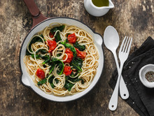 Vegetarian Whole Grain Spaghetti Pasta With Cherry Tomatoes And Spinach Sauce In A Cast Iron Pan On A Wooden Background, Top View. Copy Space, Healthy Diet Food Concept