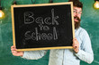 Start of school year concept. Teacher peeking out of chalkboard. Man with beard welcomes students, chalkboard on background. Teacher on cheerful face holds blackboard with title back to school.