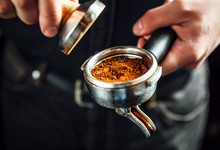 Barista Holding Portafilter And Coffee Tamper Making An Espresso Coffee.