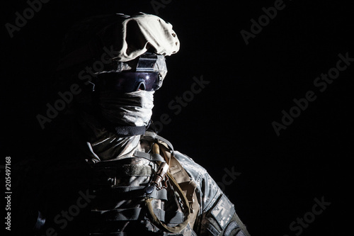 Foto Close up portrait of modern infantry soldier, active army fighter, military mercenary in helmet, face hidden with balaclava and glasses high contrast, cropped on black background