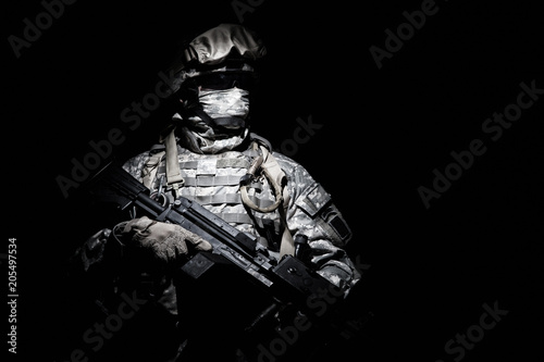 Photo  United States Armed Forces soldier in battledress with black glasses and mask on face, armed squad automatic weapon emerges from darkness