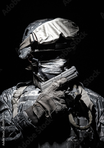 Fotografia, Obraz  Special operations forces soldier in combat helmet with hidden behind balaclava and dark glasses face posing with sidearm service pistol in hand