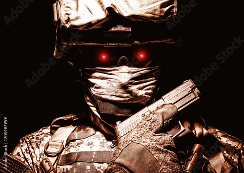 Fototapeta Special operations forces soldier in combat helmet with terrible burning red eyes posing with sidearm service pistol in hand