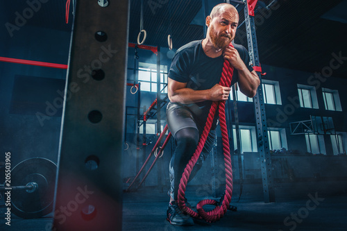 Fotobehang Wintersporten Men with battle rope battle ropes exercise in the fitness gym. CrossFit.