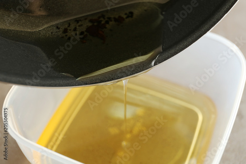 Fototapeta Pouring used cooking oil from frying pan into plastic container, closeup obraz