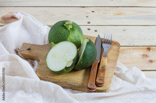Green zucchini balls. Wooden table and board.