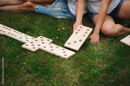 Fotografía Young man and woman playing giant dominoes in the Park on the grass