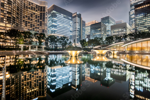 Staande foto Aziatische Plekken Cityscape in the Marunouchi business district of Chiyoda with skyscrapers reflected in the fountain taken in a cloudy night, Tokyo, Japan