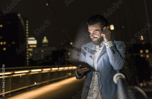 Young man on bridge at night with world map emerging from tablet
