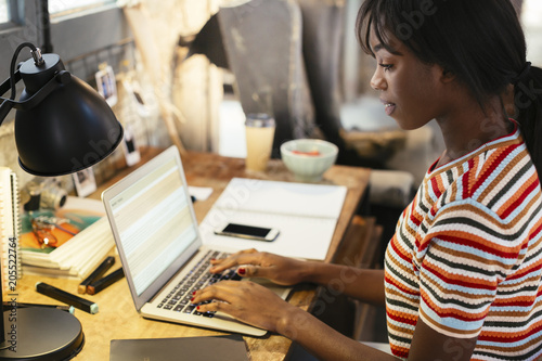 Young woman sitting at desk working on laptop