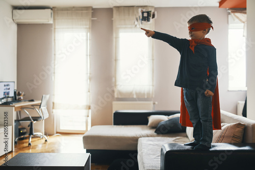 Little boy dressed up as a superhero standing on coffee table at home pointing on something