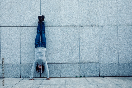 Fotomural  female hipster doing a handstand against wall