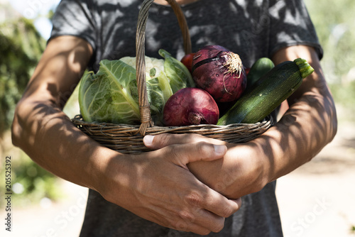 Foto young man with a basket full of vegetables