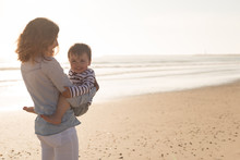 Mother At The Beach With Her Baby