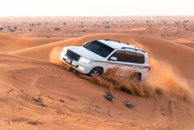 Safari On Jeeps SUVs In The Arab Orange-red Sands In The Sunset Sun. Column Of Sand Of  Wheels,