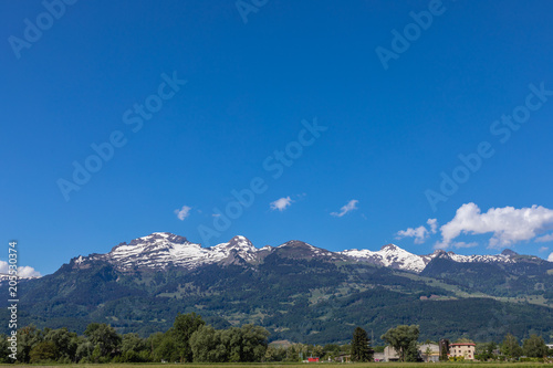 Foto op Aluminium Alpen View of the green field and mountains of the Alps in Liechtenstein.