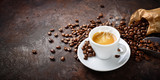 Fototapeta Kawa jest smaczna - Espresso and coffee beans on plaster background