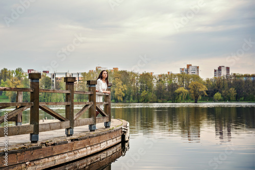 Photo thinking woman in white dress is standing on a wooden pontoon bridge on a river